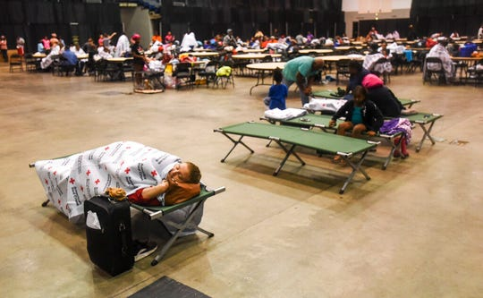 People rest on cots and blankets supplied by the American Red Cross at the Beaumont Civic Center after the Center was opened as an emergency shelter Thursday morning, Sept. 19, 2019,  in downtown Beaumont, Texas.