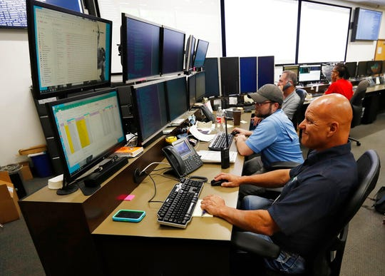 In this Sept. 12, 2019, photo, monitors check their screens in the Governor's Office of Information Technology in Denver. Some cybersecurity professionals are concerned that insurance policies designed to limit the damage of ransomware attacks might actually be encouraging hackers.