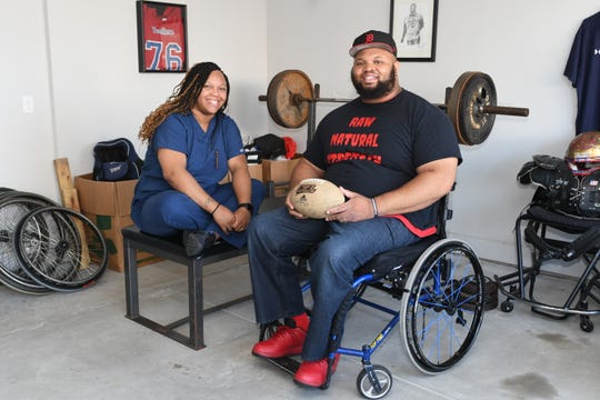 Paraplegic power lifter Antonio Martin, wounded in a Detroit shooting sits in his home weight room in Utica with his wife Melanie, holding a football as he recalls his time playing football at Martin Luther King Jr. High School in Detroit. Martin, is set to qualify on the US Paralympic Team for the Tokyo 2020 Summer Games.