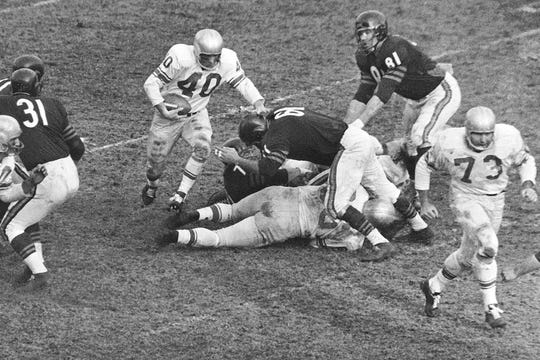 In this Dec. 14, 1959, file photo, Detroit Lions back Howard Cassady shoots toward a big hole in the Chicago Bears defense during the third quarter of a football game Chicago, Ill.