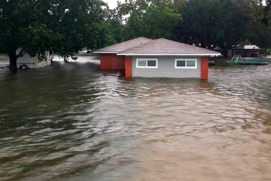 In this photo provided by the Chambers County Sheriff's Office, floodwaters surround a home, Thursday, Sept 19, 2019, in Winnie, Texas.