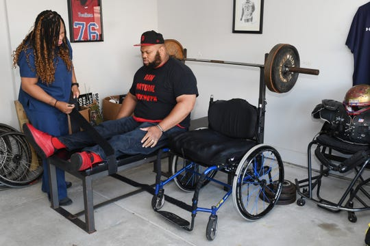 Power lifter Antonio Martin is strapped onto his weight bench with help from his wife Melanie at their home in Utica. Martin, is set to qualify on the US Paralympic Team for the Tokyo 2020 Summer Games.