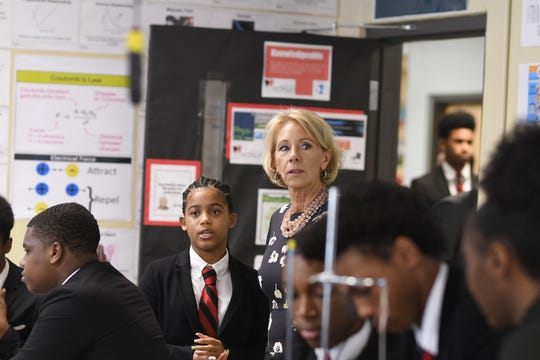 U.S. Secretary of Education Betsy DeVos enters the principal of engineering class at Detroit Edison Public School Academy with student Mai'ja Hinton on Friday.