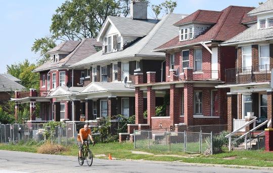 Developer Ron Castellano rides his bike near the former Herman Kiefer Hospital site and around the Virginia Park neighborhood.