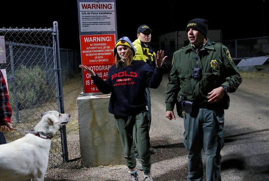 Sheriff's deputies escort a woman who ducked under the gate at an entrance to the Nevada Test and Training Range near Area 51 Friday, Sept. 20, 2019.