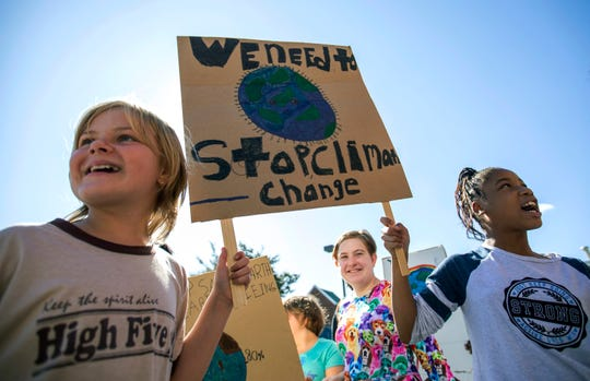 """Haley Williams, left, and Amiya Cox hold a sign together and chant while participating in a """"Global Climate Strike"""" at the Experiential School of Greensboro in Greensboro, N.C., on Friday, Sept. 20, 2019."""
