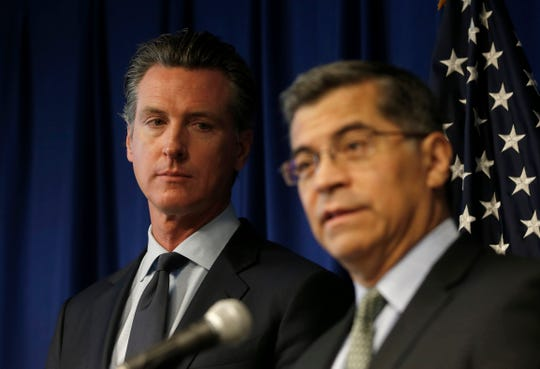 Gov. Gavin Newsom, left, listens to Attorney General Xavier Becerra, as he discusses the Trump administration's pledge to revoke California's authority to set vehicle emissions standards that are different than the federal standards.