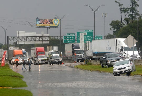 Stopped trucks on I-10 and flooded cars lining the frontage road are seen as people make their way across the road in Beaumont, Texas, where several roads remained heavily flooded throughout the afternoon on Thursday, Sept. 19, 2019. Boaters and other emergency personnel were conducting rescue missions to those in need throughout the morning and afternoon.