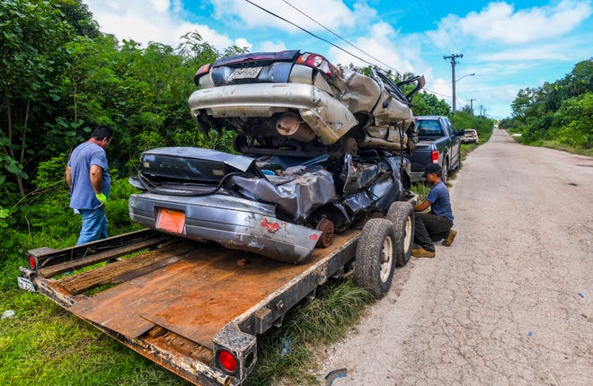A load of crushed vehicle are secured to a trailer in preparation of being transported from a home along Swamp Road in Dededo on Thursday, Sept. 19, 2019.