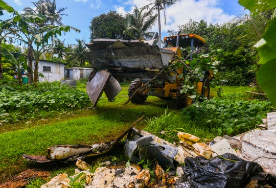 A Department of Public Works employee uses a back-hoe to load an old refrigerator in to a dump truck after removing the appliance from a home along Swamp Road in Dededo on Thursday, Sept. 19, 2019. Health officials and other responding government agencies have been concentrating their efforts within a 200-meter radius of the second patient diagnosed to have locally acquired a case of dengue fever. Efforts include the removal of old tires, vehicles, old appliances and other items that may collect water and serve as a breeding container for mosquitos which could spread the disease.