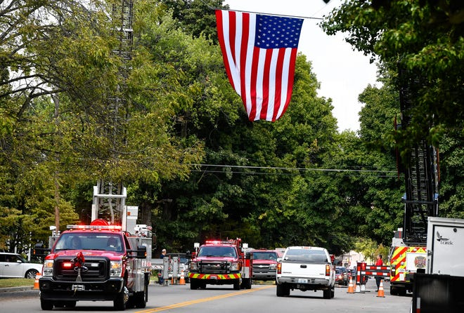 Fire trucks in the funeral procession for longtime Niagara Fire Chief Hilary Thompson pass under a giant American Flag, suspended from  ladder trucks, as it makes its way down South Main to St. Louis Cemetery Friday.