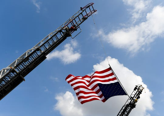 A giant American Flag is suspended over South Main Street in Henderson from a pair of local ladder trucks for the funeral procession of longtime Niagara Fire Chief Hilary Thompson,Friday.