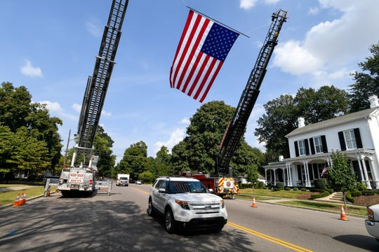 The funeral procession for longtime Niagara Fire Chief Hilary Thompson passes under a giant American Flag suspended from local ladder trucks as it makes its way down South Main Street Friday.