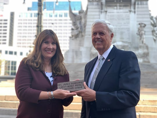 Kathy Strong poses with retired Air Force Brigadier General J. Stewart Goodwin holding a replica of the brick placed in Monument Circle on Friday.
