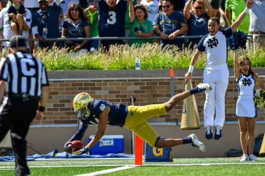 Notre Dame Fighting Irish safety Kyle Hamilton (14) dives into the end zone for a touchdown on Sept. 14 following an interception in the first quarter against the New Mexico Lobos at Notre Dame Stadium.