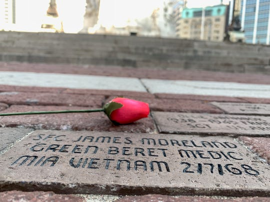 A wooden rose sits next to the memorial brick that honors James Moreland, who died during the Vietnam War.