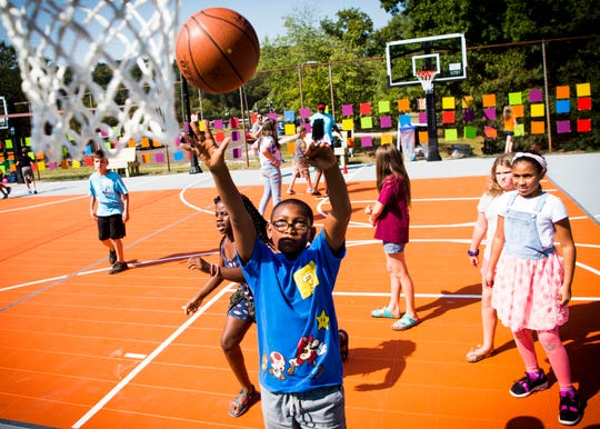Children with the Vestal Boys & Girls Club play on their new basketball court at the South Knoxville Community Center on Friday, Sept. 20, 2019.