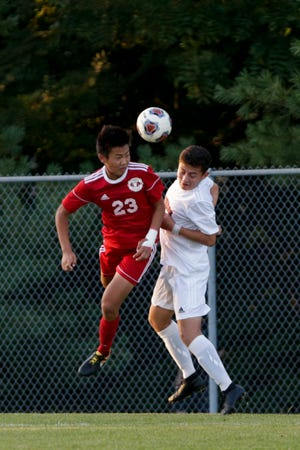 West Lafayette midfielder Michael Chen (23) heads the ball over Harrison's Evan Sengsanith (14)  during the first half of an IHSAA boys soccer match, Thursday, Sept. 19, 2019 in West Lafayette. West Lafayette won, 2-0.