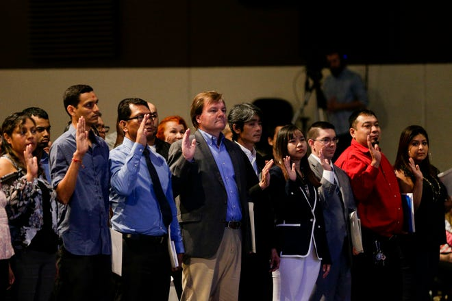 Over 90 people raise their right hands as they take the oath of citizenship during a naturalization ceremony, Friday, Sept. 20, 2019 in West Lafayette.