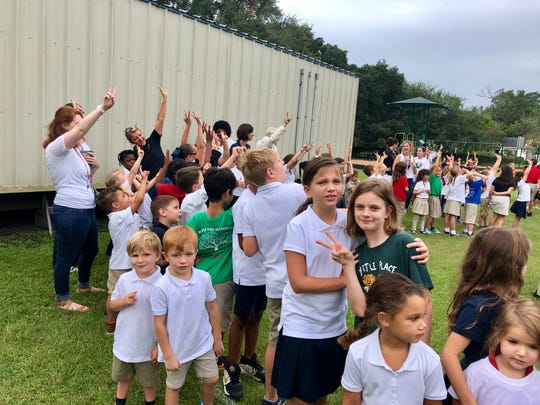 "Myrtle Place Elementary students and faculty hold up peace signs toward a drone taking pictures of them from the sky during a ceremony Friday, Sept. 20, celebrating International Day of Peace as a school. The students are standing in the shape of a giant heart and the letter P-A-I-X, which spells the French word for ""peace."""