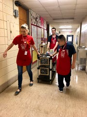 Ovey Comeaux High special education teacher Mary Alciatore-Young and students Joel and Ramon pull the Spartan Brew Crew coffee cart to deliver free coffee to teachers and staff Friday, Sept. 20.