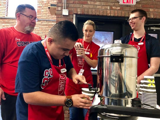 Ovey Comeaux High School students Ramon and Joel serve teachers free coffee and smiles Friday, Sept. 20, as part of the Spartan Brew Crew. Ramon pours a cup for teacher Shane Denais first thing in the morning.