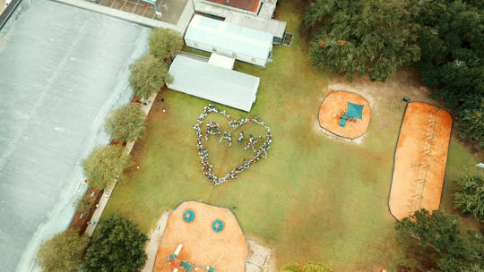 "This aerial photo taken by a drone shows Myrtle Place Elementary students and faculty the shape of a giant heart and the letters P-A-I-X, which spells the French word for ""peace,"" during a ceremony Friday, Sept. 20, celebrating International Day of Peace as a school."