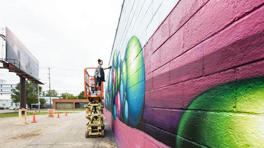 "Below the Stacks commissioned-artist Christina Wing Chow, aka ""Wingchow,"" of Richmond, Virginia works her mural Tuesday, Sept. 17, 2019, near the corner of E. Shiawassee Street and N. Larch Avenue.  Her artwork is one of eleven pieces in the citywide mural festival featuring work from new and established artists from Lansing, Detroit, and other major cities.  The event began Sept. 15th and runs through the 21st."