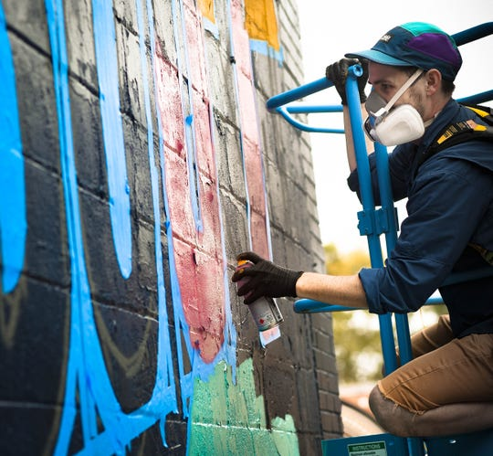 """It's a tribute to little Stevie Wonder,"" Below the Stacks co-director Dustin Hunt of Lansing said while working his mural entitled ""Heeeey Love,"" Tuesday, Sept. 17, 2019, on a vacant building across the street from Elderly Instruments in the 1100 block of N. Washington Avenue in Lansing.  ""He (Wonder) recorded four full-length albums when he was at the Michigan School for the Blind - many Lansing residents don't know that.""  Known also as ""Muralmatics,"" Hunt's piece is one of eleven being created in the citywide mural festival created by both new and established artists locally and nationwide."