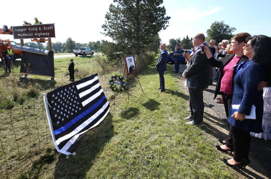 Signs honoring fallen Michigan State Police trooper Craig Scott were unveiled Friday on U.S. 127 in the Leslie area. Scott was shot and killed during a traffic stop in February 1982.