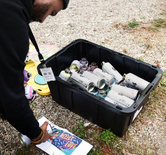 "Below the Stacks co-director Ozay Moore grabs cans of spray paint to work on the tribute mural entitled ""Heeeey Love,"" a tribute to Stevie Wonder, Tuesday morning, Sept. 17, 2019.   After moving around the country, Moore and his family returned to Lansing where he's active in the arts community.  He and co-director Dustin Hunt helped obtain grants and organize the event.  ""I used to say 'what can I get from this place?'  Now I ask, 'what can I give to this place?'"""