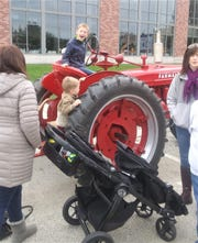 Kids climb a tractor in downtown Manitowoc during HarvestFest.
