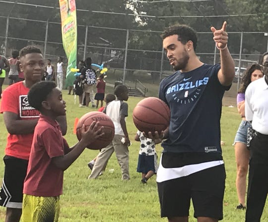 Grizzlies point guard Tyus Jones prepares to challenge a local child to a shooting competition during a Grizzlies block party at Lester Community Center on Sept. 19.