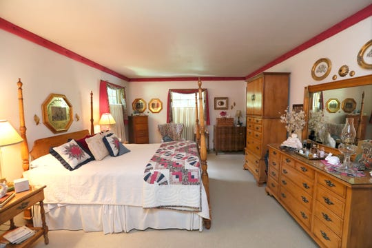 The master bedroom features a four-poster bed and Amish quilt purchased in Viroqua.