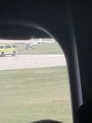 This photo, taken by a passenger who was on board a nearby aircraft, shows a small single engine plane in a grassy area of Milwaukee Mitchell Airport on Friday.