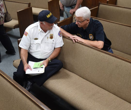 Mountain Home Fire Chief Ken Williams (left) talks with Mountain Home Police Chief Carry Manuel (right) after the conclusion of Thursday night's City Council meeting.