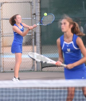Mountain Home's Sarah Godfrey returns a shot as doubles teammate Macie Heide (foreground) looks on against Searcy on Thursday.