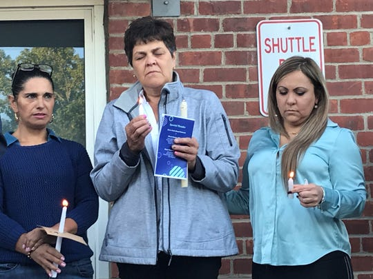 Beatriz Gomez-Restrepo, pictured in the center, closes her eyes as she prays for her son during Friday nights prayer vigil for the teen.