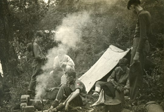 Boy Scout Troop 33 members tend a smoky fire as they gather around a pup tent at a campsite at Camp Red Wing in this photograph from 1939.