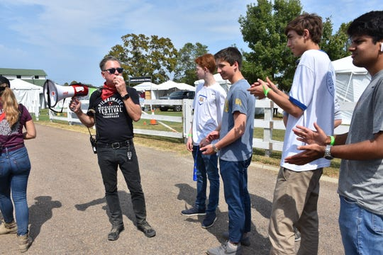 Brandt Wood tells students about the different stages on the grounds of Pilgrimage Music & Cultural Festival on Friday.