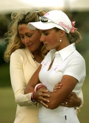 ** FILE ** Kelly Jo Dowd, left, hugs her daughter Dakoda after she finished her second round of play at the Ginn Open LPGA golf tournament in Reunion, Fla., on in this April 28, 2006 file photo. Kelly Jo Dowd, a cancer-stricken mother whose dream of seeing her teen daughter Dakoda play in an LPGA event was realized last spring, died Thursday night, May 24, 2007, at her home in Palm Harbor, Fla., a family spokesman said. She was 42. (AP Photo/John Raoux)