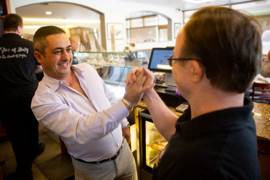 Cosmos Ristorante & Pizzeria owner Gianluca Corso gives a high-fives to his employee Shawn Denton after Corsco was presented an award by STARAbility for hiring employees with special needs, Thursday, Sept. 19, 2019 in Naples.