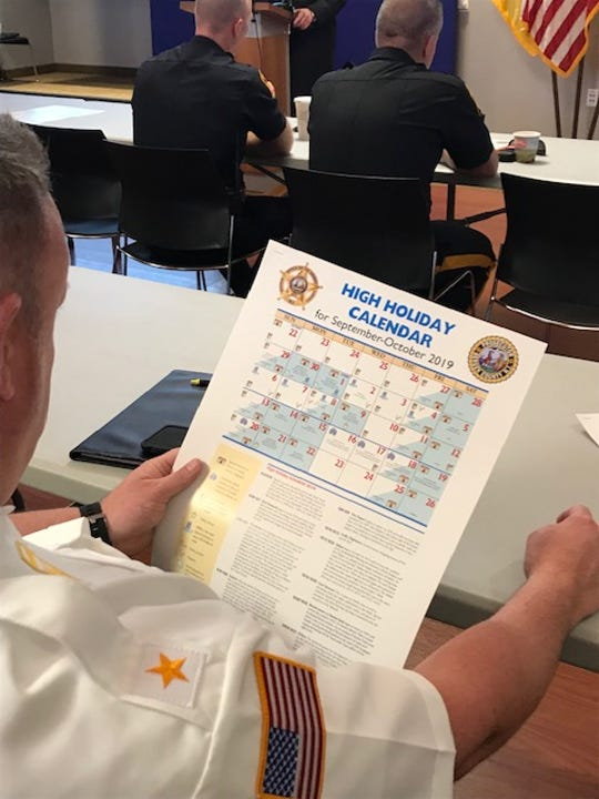 Law Enforcement gathered in Hackensack to discuss synagogue security. Pictured is a police officer examining a schedule of Jewish holidays and explanation of various holiday customs.