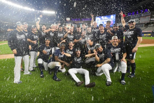 The New York Yankees celebrate after defeating the Los Angeles Angels and clinching the AL East title, Thursday, Sept. 19, 2019, in New York.