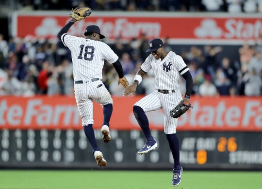 Didi Gregorius #18 and Cameron Maybin #38 of the New York Yankees celebrate the 9-1 win over the Los Angeles Angels at Yankee Stadium on September 19, 2019 in New York.