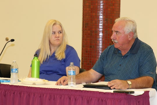 Mary Garwood, left, and Dave Sepich talk about efforts to control littering in the City of Carlsbad Sept. 19 during the Eddy County Energy Advisory Board meeting.