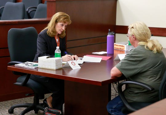 Patricia Simpson, left, of the Simpson Law Office, talks with a resident of Aztec on Friday, Sept. 16, 2016, during the 6th Annual Legal Fair at the Eleventh Judicial District Court in Aztec.