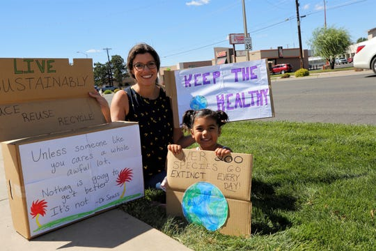 Cynthia Rapp Sandhu and her daughter Zaira, 4, hold signs they made, Friday, Sept. 20, 2019, for the Global Climate Strike event in Farmington.
