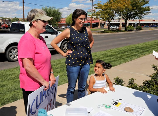 Zaira Sandhu, 4, fills out a postcard, Friday, Sept. 20, 2019, as her mother, Cynthia Rapp Sandhu, center, and Joan Arrowsmith, left, help her during the Global Climate Strike in Farmington.