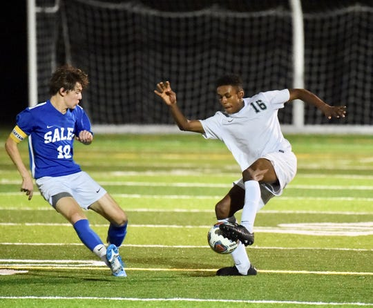 Novi's Miles Brown makes a move to get past Salem's Ethan Harkins.